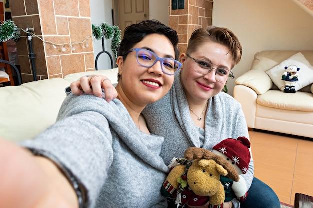 リビングルームでクリスマスのぬいぐるみ雪だるまとトナカイと一緒に自分撮りをしている2人の女性の若いカップル
