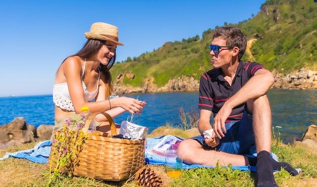 Молодая пара на пикнике пьет апельсиновый сок в горах у моря, наслаждаясь летом