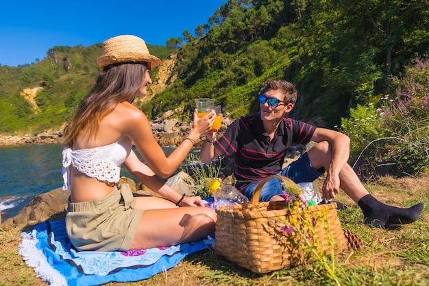 Молодая пара на пикнике с апельсиновым соком в горах у моря, наслаждаясь летом