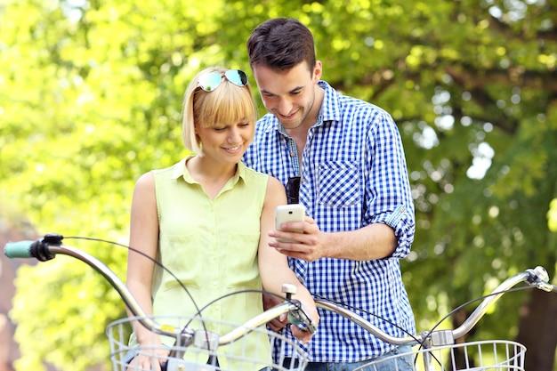 携帯電話で自転車に乗っている若いカップル