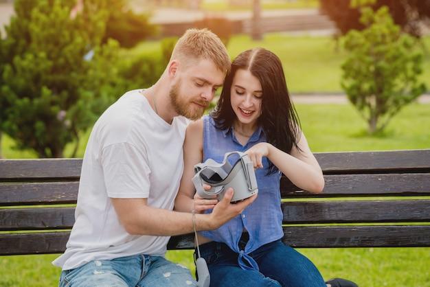 若いカップルが路上で仮想現実の眼鏡を使用してゲームをプレイします。