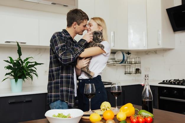 若いカップルがモダンなキッチンで健康的な夕食を準備します。