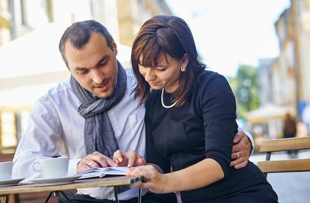 通りのカフェで本を読んでいる若いカップル