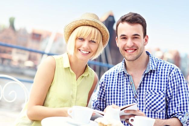 レストランでガイドを読んでいる若いカップル