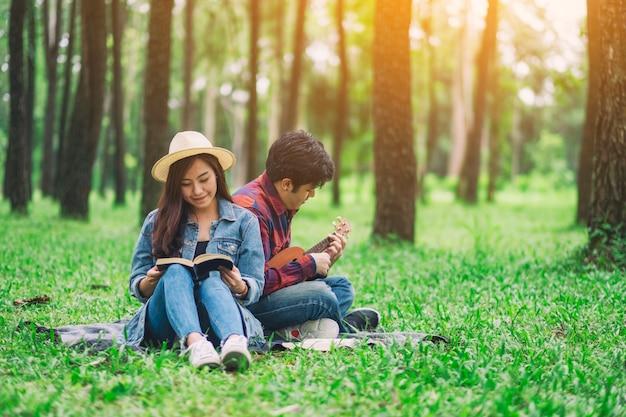 Молодая пара читает книгу и играет на укулеле, сидя в лесу