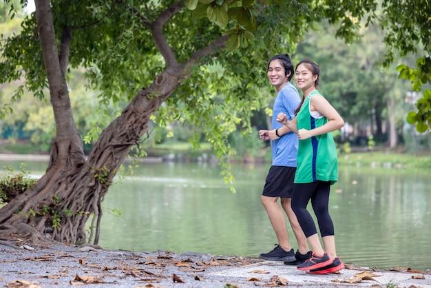 Молодая пара, бегающая по парку, спорт и любовь сочетаются в этой концепции, а спортивный мужчина и женщина тренируются вместе. Premium Фотографии