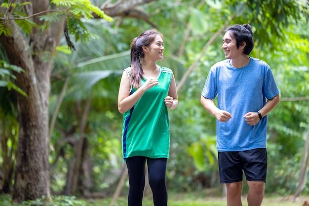 Молодая пара, бегающая по парку, спорт и любовь сочетаются в этой концепции, а спортивный мужчина и женщина тренируются вместе.