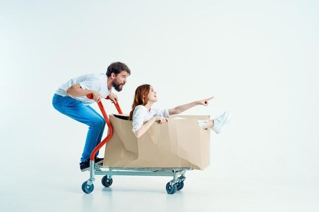 Молодая пара, доставка транспорта в коробке изолированном фоне