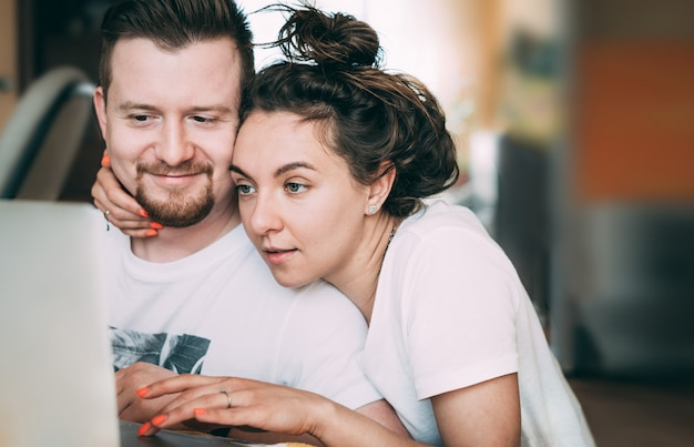 Молодая пара сидит дома и планирует свои покупки и свадьбу.