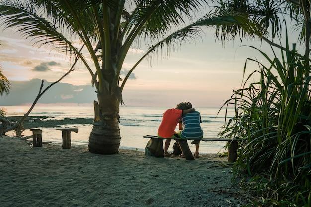 若いカップルがヤシの木の下のベンチに座って、海に沈む夕日を眺めています。エキゾチックな島の新婚旅行のカップル。愛とロマンスの概念。海に沈む夕日をお楽しみください。イブニングライト