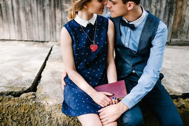 Молодая пара сидит и обнимается держит в руках закрытую книгу возле старого деревянного дома с окнами