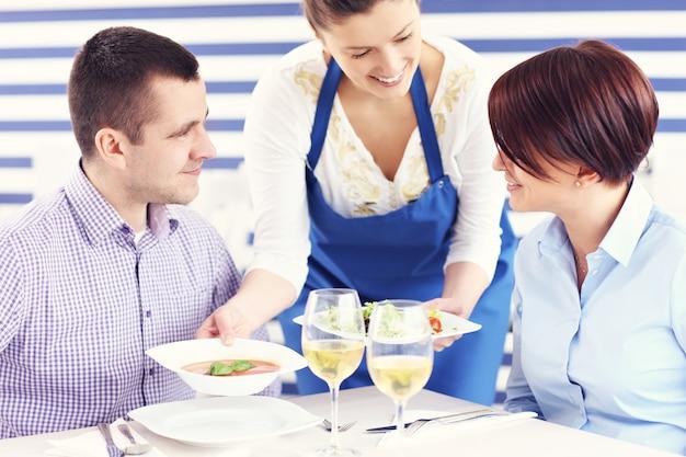 Молодая пара сидит в ресторане и обслуживается