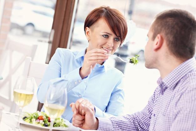 Молодая пара сидит в ресторане и ест