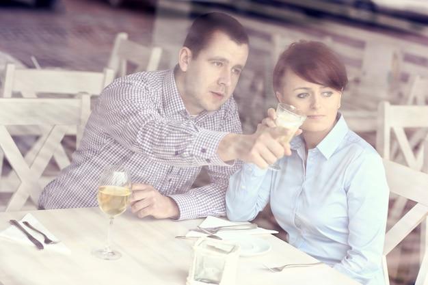 식당에 앉아 창문을 통해 찍은 사진을 가리키는 젊은 부부