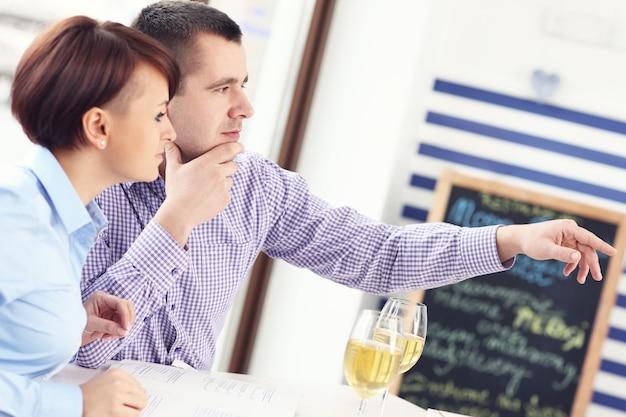 레스토랑에 앉아 뭔가를 가리키는 젊은 부부