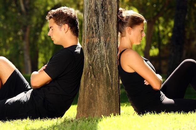 公園に座って紛争にある若いカップル