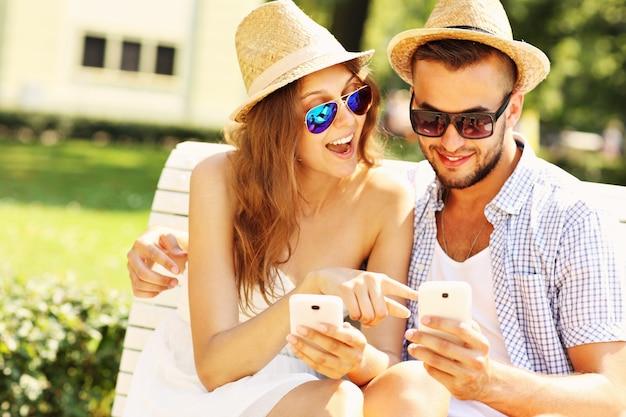 Молодая пара сидит на скамейке со смартфонами