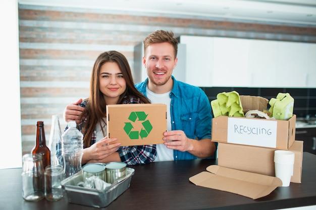 若いカップルが台所でゴミを分別します。若い男性と女性が台所でリサイクル可能なものを分類しています。段ボール、紙、鉄、プラスチック、ガラス、その他のリサイクル可能な材料があります。