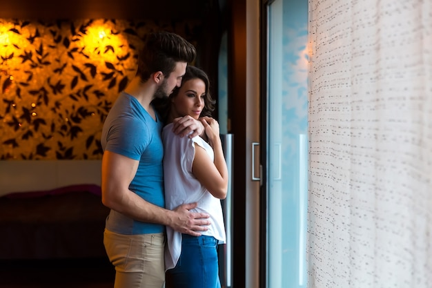 恋を抱きながら家の窓際に立っている若いカップル。