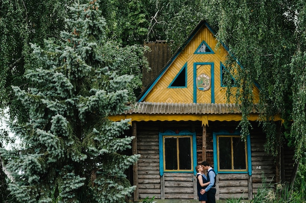 若いカップルが立って、抱き合って、森の島の古い木造の家の近くにキス