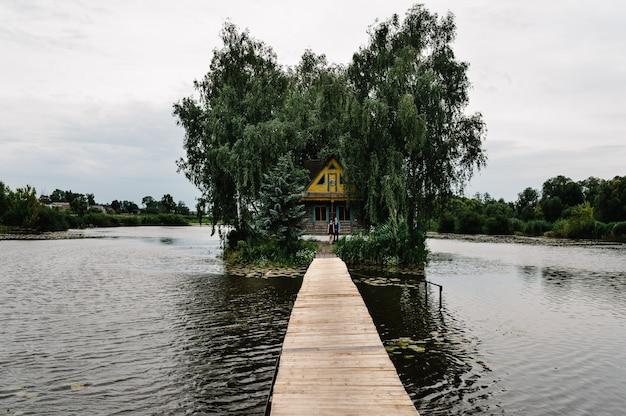 湖の真ん中にある島の古い木造の家の近くに立っている若いカップル