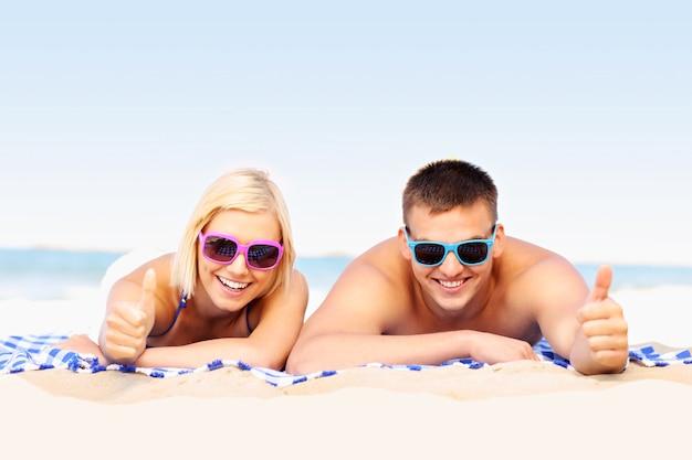 ビーチで日光浴をしている若いカップル