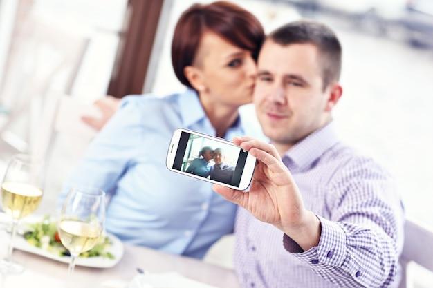 Молодая пара фотографируется в ресторане
