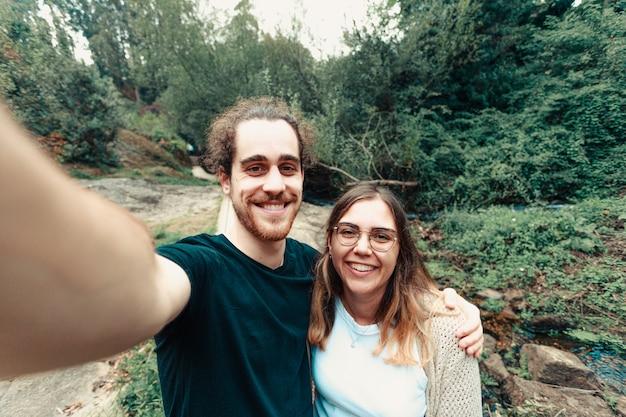 Молодая пара делает селфи в лесу, улыбаясь