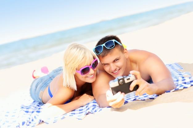ビーチで写真を撮る若いカップル