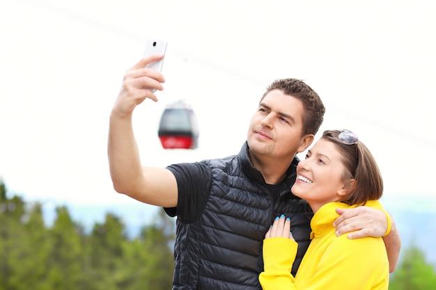 ゴンドラを背景に山で写真を撮る若いカップル