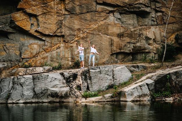 Молодая пара бросает камни в воду на поверхности скал