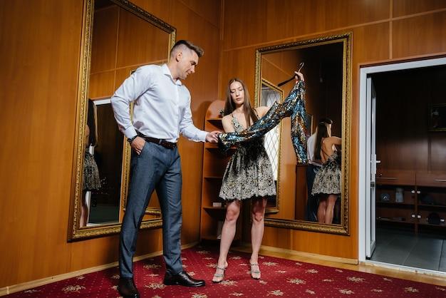 若いカップルがスーパーで買い物をしている店の試着室で新しい服を試着します。