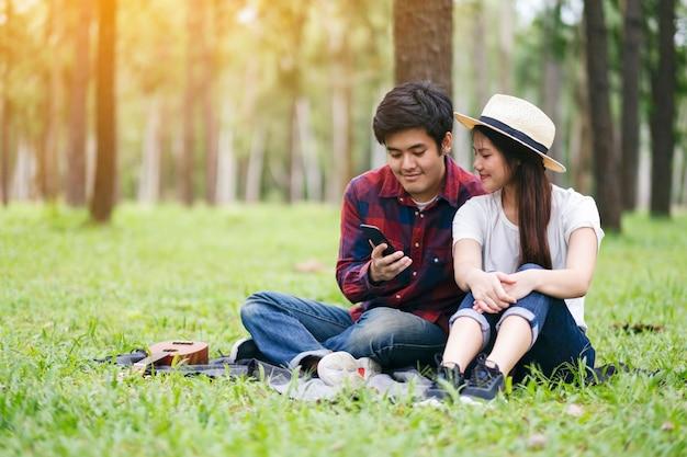 Молодая пара, сидящая в парке вместе с мобильным телефоном