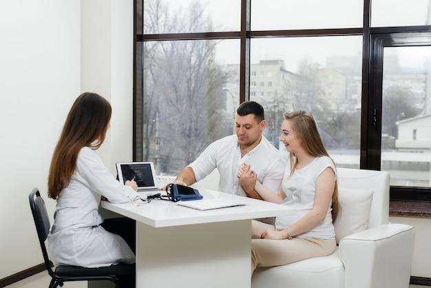 超音波検査の後、赤ちゃんが婦人科医に相談するのを待っている若いカップル。妊娠、そして健康管理。
