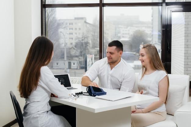 超音波検査後、赤ちゃんが産婦人科医に相談するのを待っている若いカップル