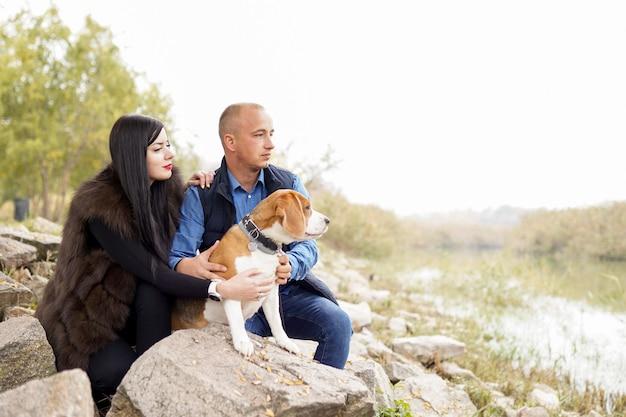 Молодая пара гуляет с собакой в парке
