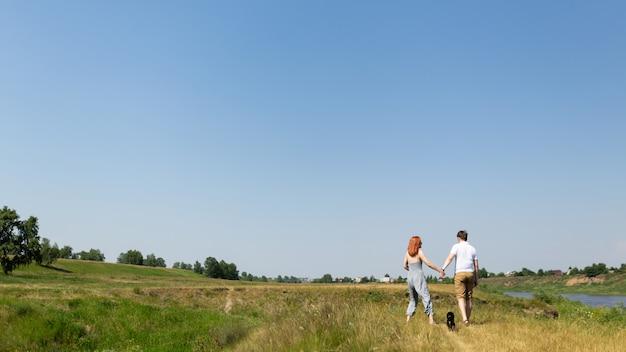 Молодая пара гуляет на природе с собакой и держась за руки