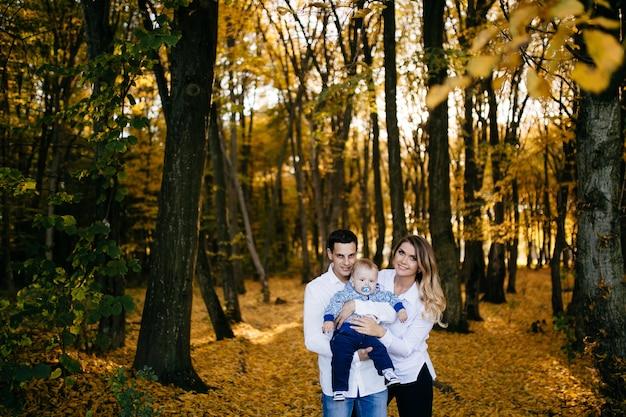 Молодая пара гуляет в лесу с маленьким мальчиком