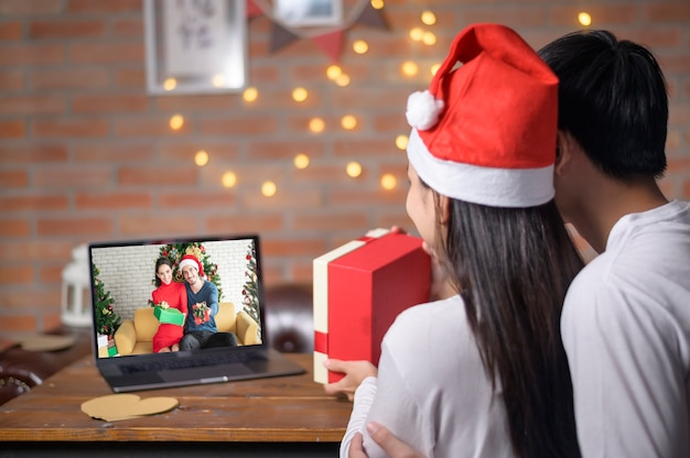 クリスマスの日に家族や友人とソーシャルネットワークでビデオ通話をしている赤いサンタクロースの帽子をかぶった若いカップル。