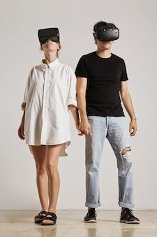 흰 벽과 나무 바닥이있는 방에서 서로 다른 방향으로보고 손을 잡고 vr 헤드셋을 착용 한 젊은 부부