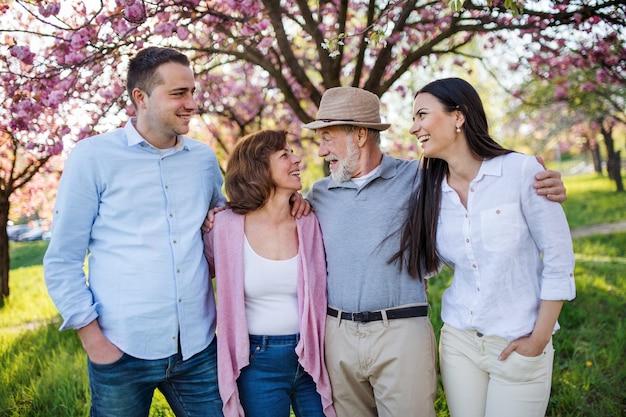 Молодая пара со старшими родителями, прогулки на свежем воздухе в весенней природе.