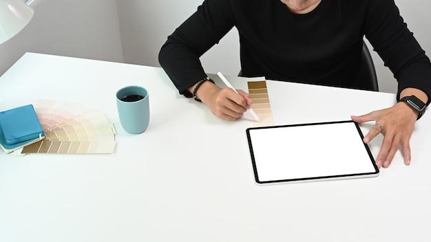 디지털 태블릿 및 색상 견본을 사용하여 프로젝트 드로잉에서 작업하는 젊은 크리에이티브 그래픽 디자이너.