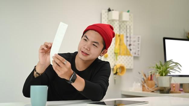 색상 견본 및 작업 도구 및 장비로 프로젝트 선택 색상을 지정하는 젊은 크리에이티브 그래픽 디자이너.