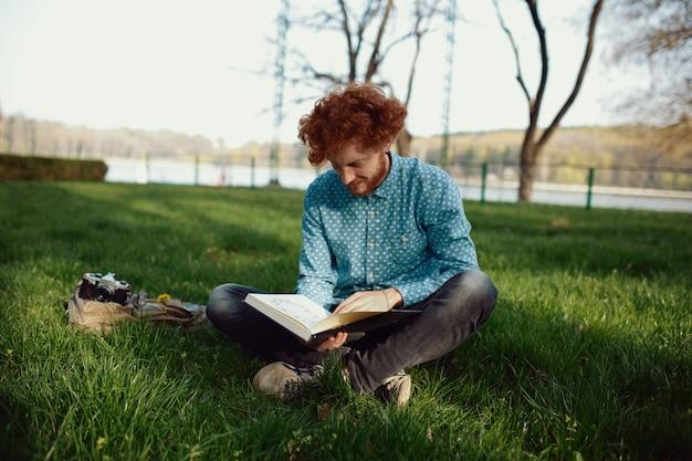 Молодой кудрявый рыжий мужчина верхом на книге, отдыхая на траве в парке