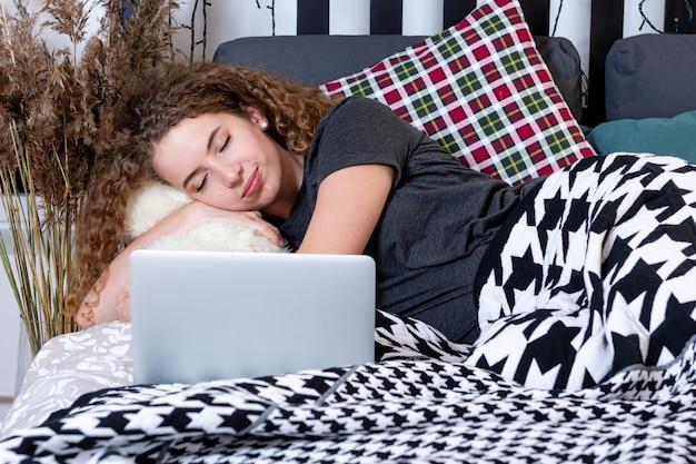 Молодая кудрявая девочка-подросток с плюшевым мишкой заснула в постели рядом с ноутбуком