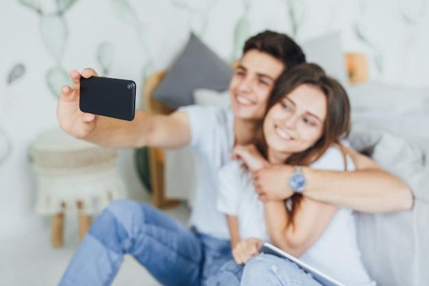 젊고 귀여운 커플이 침대 근처 별장에서 집에서 자신을 촬영합니다