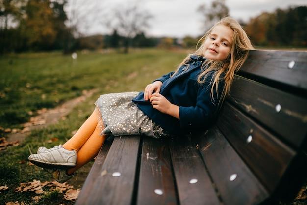 ベンチでポーズをとって若いかわいい女の子