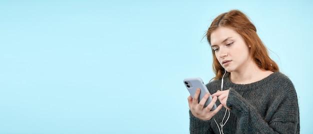 어린 귀여운 소녀가 헤드폰으로 전화를 통해 더 들을 수 있도록 자신이 좋아하는 음악을 선택합니다. 음악 모바일 앱 자신감이 있는 학생 텍스트 복사 공간