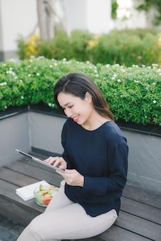 タブレットをスクロールして働いている公園に座っている若いかわいい女の子