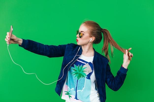 長い髪の尾を持つかわいい少女は、背景の緑の壁の近くでselfieを作っています。彼女はハートのサングラスをかけ、唇は赤い。彼女はヘッドフォンで音楽を聴いています。
